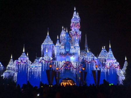 Photo of Sleeping Beauty Castle at Disneyland, covered in fake snow and lights as part of the holiday decorations.